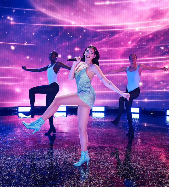 Dua Lipa performed at the 2020 American Music Awards wearing blue crystal ankle boots and a matching mini dress.