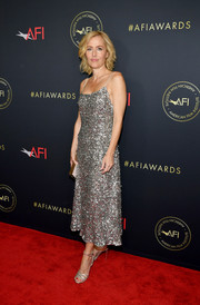Gillian Anderson kept the shine going with a pair of strappy silver heels.