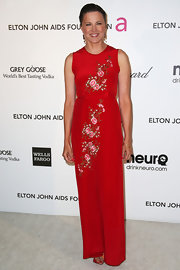 Lucy Lawless looked feminine and soft in a red dress with floral detailing while attending Elton John's Oscar party.