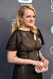 Elisabeth Moss arrived for the 2018 Critics' Choice Awards carrying a nude hard-case clutch by Tyler Ellis.