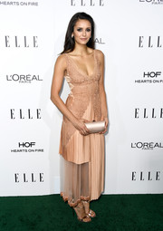 Nina Dobrev polished off her monochromatic ensemble with a champagne satin tube clutch by Rodo.