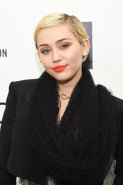 Miley Cyrus looked uncharacteristically tame with her neat boy cut during Elton John's Oscar-viewing party.