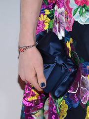 A navy satin clutch complemented Anne Hathaway's floral dress.