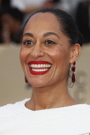 Tracee Ellis Ross accessorized with a pair of red gemstone drop earrings by Lorraine Schwartz for a splash of color to her white dress.