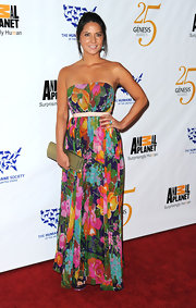 Olivia Munn paired her floral maxi dress with a gold snakeskin clutch.