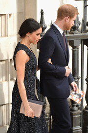 Meghan Markle paired a nude Wilbur & Gussie satin clutch with a black print dress for the 25th anniversary memorial service celebrating Stephen Lawrence.