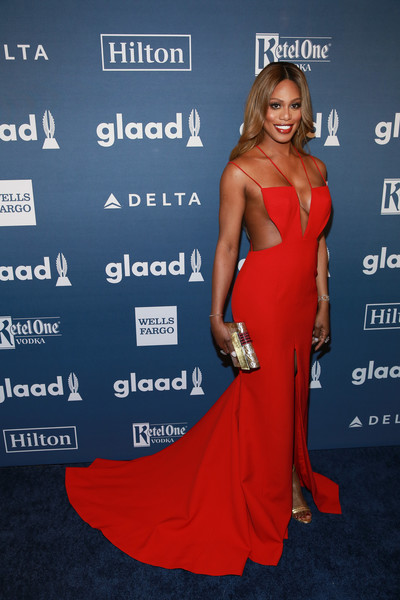 Laverne Cox's metallic gold clutch worked beautifully with her red gown.