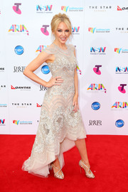 Kylie Minogue complemented her dress with strappy gold sandals by Christian Louboutin.