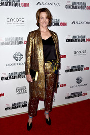 A pair of black velvet pumps with blue ankle straps finished off Sigourney Weaver's look.
