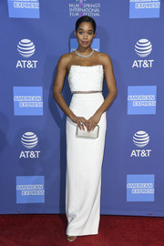 Laura Harrier matched her dress with a white satin clutch.