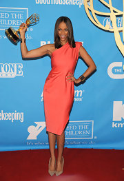 Tyra brandishes her Emmy award with pride in a coral one-shoulder dress.