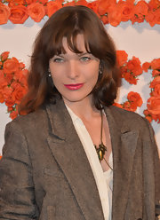 Milla Jovovich swiped her lips with a glossy lipstick in a hot pink hue.