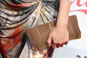 Jeannie Mai accessorized with a unique metallic gold zipper clutch when she attended the Streamy Awards.