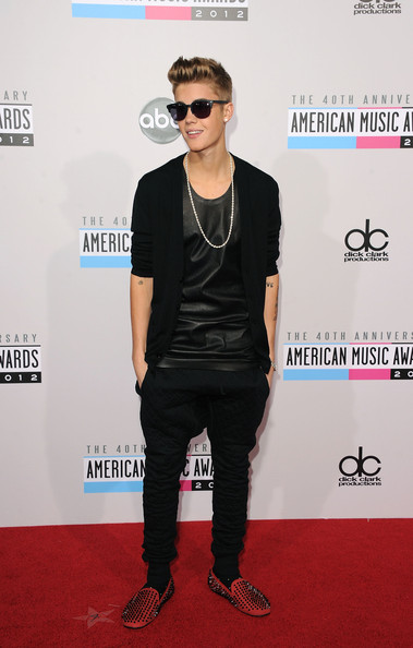 Justin Bieber finished off his sleek black style with a pair of bright-red studded smoking slippers.