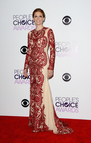 Stana Katic worked a regal vibe in this Naeem Khan number, featuring intricate red embroidery against a sheer nude background, during the People's Choice Awards.
