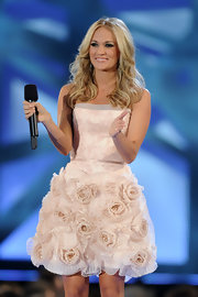 Carrie dons a darling pink cocktail dress for one of her many wardrobe changes at the CMAs. The strapless pink dress is detailed with darling flower embellishments.