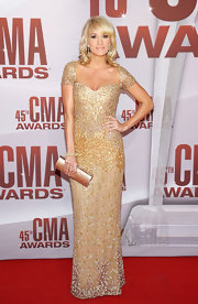 Carrie Underwood accented her intricately beaded gold gown with a matching hard case clutch at the 2011 CMAs.