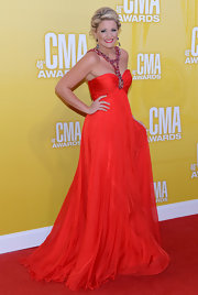 American Idol's Lauren Alaina was on fire at the CMAs in this red hot chiffon gown. Her lips matched her ensembles and she wore her usual sky-high locks in a tamed updo.