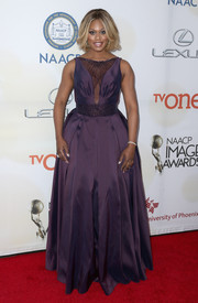 Laverne Cox's purple Gustavo Cadile gown at the NAACP Image Awards had an old-worldly feel with its exaggeratedly flared skirt.