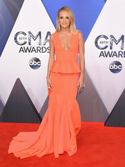 Carrie Underwood went for ultra-feminine appeal in a low-cut coral peplum gown by Gauri & Nainika at the CMA Awards.