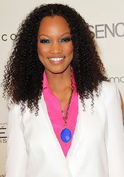 Garcelle Beauvais showed off her natural curls at the Essence Black Women luncheon with a simple center part hairstyle.