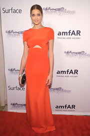 Ana Beatriz Barros wore a vibrant orange capped-sleeve dress with a triangular cutout under the bust.