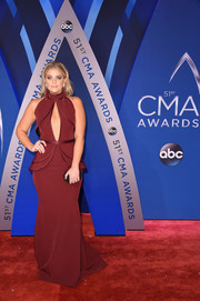 Lauren Alaina flashed her cleavage in a maroon keyhole gown with peplum detailing at the 2017 CMA Awards.