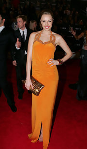 Jessica McNamee showed off her bright side in a mandarin orange dress. She paired her dress with a metallic bronze clutch.