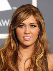 Miley Cyrus amped up her bronzed look with fluttering lashes at the 53rd Grammy Awards.