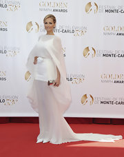 Adriana Karembeu chose a sheer white gown with a long flowing train and a matching cape for her look at the Monte Carlo TV Festival Closing Ceremony.