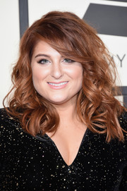 Debuting a darker hair color, Meghan Trainor wore bouncy curls with side-swept bangs when she attended the Grammys.
