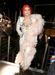 Lady Gaga post backstage at the Grammys wearing a pale pink marabou boa.