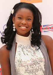 Coco Jones flaunted her femininity in a pair of intricate white dangling earrings at the Kidstock Music and Arts Festival.