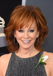 Reba McEntire sported a teased, wavy hairstyle with wispy bangs at the 2018 Grammys.