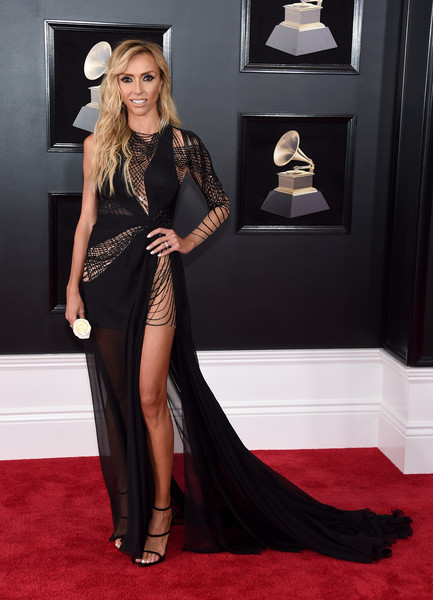 Giuliana Rancic went majorly sultry at the 2018 Grammys in a black Mikael D fishtail gown with a waist-high slit and mesh-accented see-through panels.