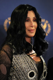 Cher contrasted her edgy outfit with a feminine wavy 'do when she attended the Directors Guild of America Awards.