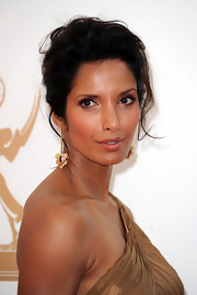 Padma Lakshmi wore her hair in a casual updo to the 63rd Emmys. Her look can be recreated by setting long hair in hot rollers and then pulling up into a loose ponytail. The ends of hair can then be twisted and looped in a variety of ways and secured with bobby pins.