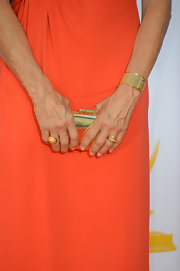 Jessica Lange accessorized her bright orange gown with shimmering gold accessories, like this metallic frame clutch.