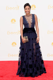Alicia Quarles selected a midnight navy sheer cutout gown, which she embellished with green gemstone jewelry.