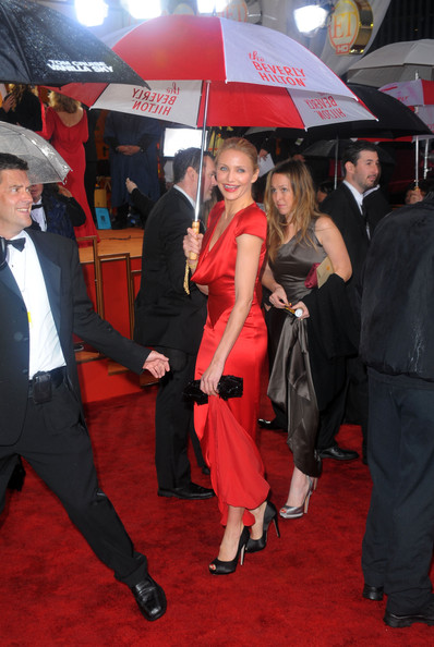 The Beverly Hilton gets some extra press coverage when Cameron Diaz carries their oversized umbrella, in red and white.