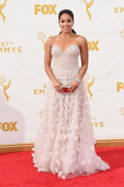 Gina Rodriguez mesmerized on the Emmys red carpet in a Lorena Sarbu strapless gown accented with beads on the bodice and tufts of cloud-like fabric on the skirt.