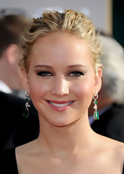 Jennifer Lawrence paired her glowing complexion with luxurious emerald green earrings.
