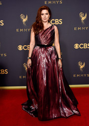Debra Messing went for high-octane glamour in a burgundy liquid-satin one-shoulder gown by Romona Keveza at the 2017 Emmys.