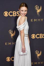 Halston Sage matched a pearlescent clutch with a white cold-shoulder gown for the 2017 Emmys.