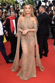 Rita Ora went for exotic glamour in a sheer, embellished Elie Saab Couture gown with shoulder cutouts and floor-grazing sleeves at the Cannes Film Festival 70th anniversary event.