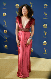 Sandra Oh looked supremely elegant at the 2018 Emmys in a crimson Ralph & Russo Couture column dress with a plunging neckline and an embellished waist and sleeves.