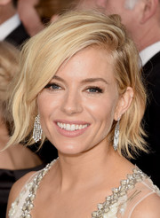 Sienna Miller complemented her bedazzled dress with a pair of diamond chandelier earrings by Tiffany & Co.