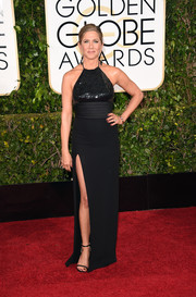 Jennifer Aniston kept it sleek and sophisticated at the Golden Globes in a black Saint Laurent halter gown with a sequined bodice and an up-to-the-hip slit.