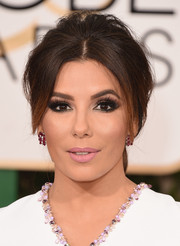 Eva Longoria styled her hair into a loose, teased ponytail with center-parted bangs for the Golden Globes.