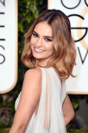 Lily James finished off her look with boho-glam waves.